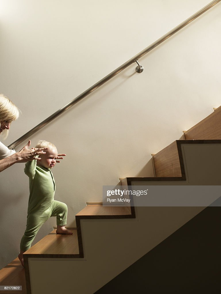 Mother helping baby boy walk up stairs : Stock Photo
