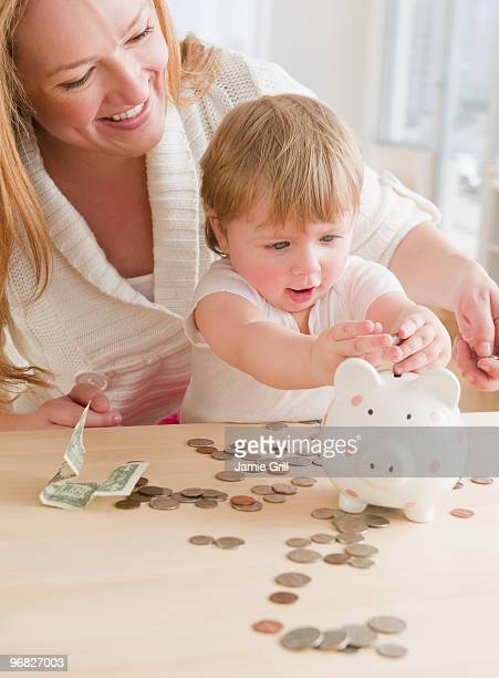 Mother helping baby girl put coins in piggy bank
