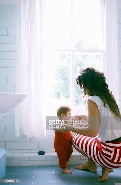 mother helping baby to stand in bathroom