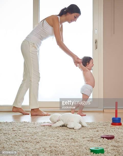 Mother helping baby walk on living room floor
