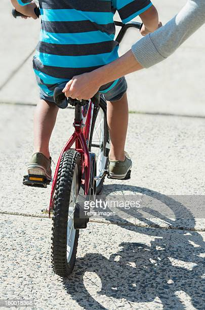 Mother helping boy (6-7) ride bicycle