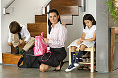 Mother helping children (6-10) get ready for school
