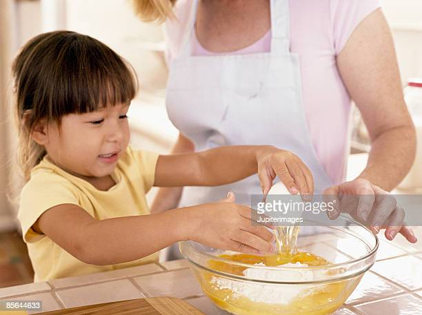 Mother helping daughter crack an egg
