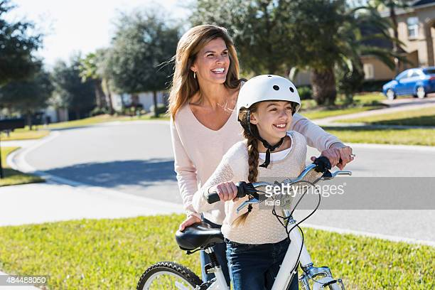 Mother helping daughter get on bicycle