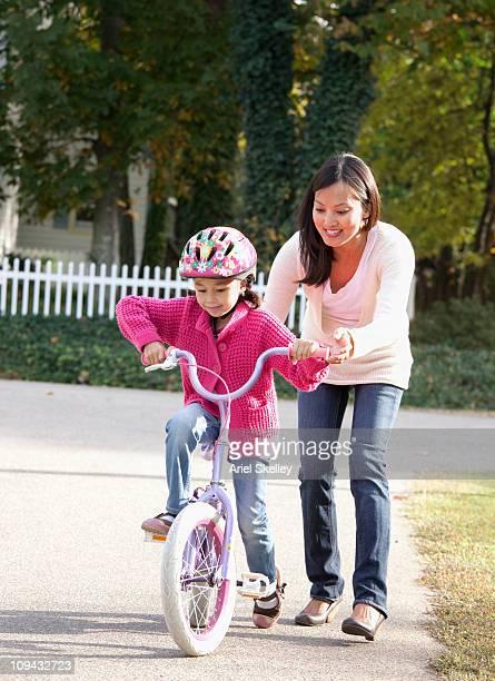 Mutter hilft Tochter lernen Sie mit dem Fahrrad