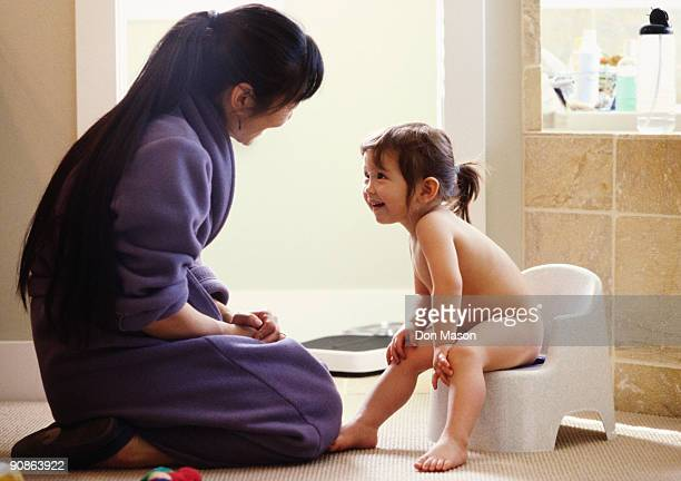 Mother helping daughter on potty chair