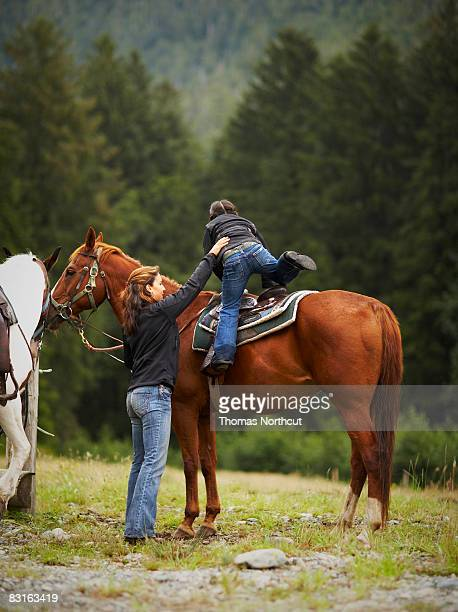 Mother helping daughter onto horse