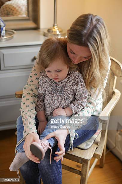 Mother helping daughter put on shoe