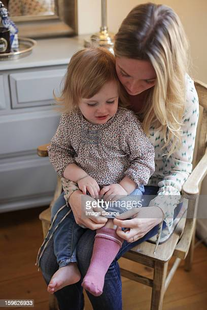 Mother helping daughter put on socks
