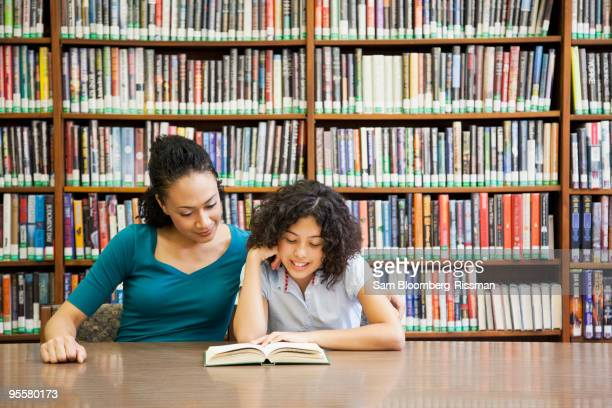 Mother helping daughter read book in library