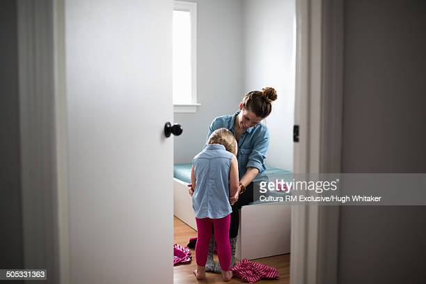Mother helping daughter to dress