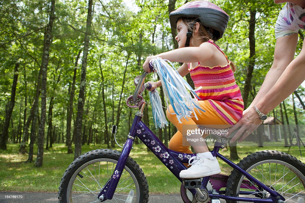 Mother helping daughter to ride bicycle : Stock Photo