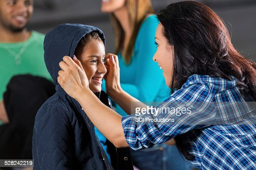 Mother helping daughter try on coat at donation drive