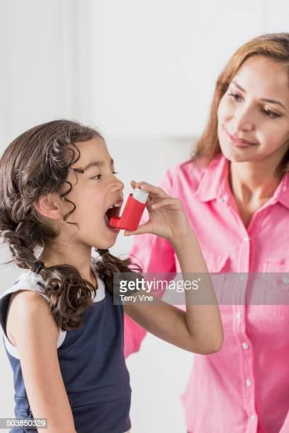 Mother helping daughter use inhaler