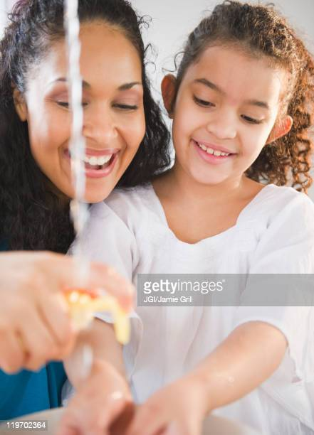 Mother helping daughter washer her hands