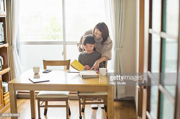 Mother helping daughter with homework in dining room