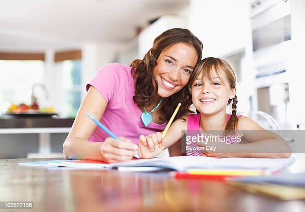Mother helping daughter (8-9) with homework