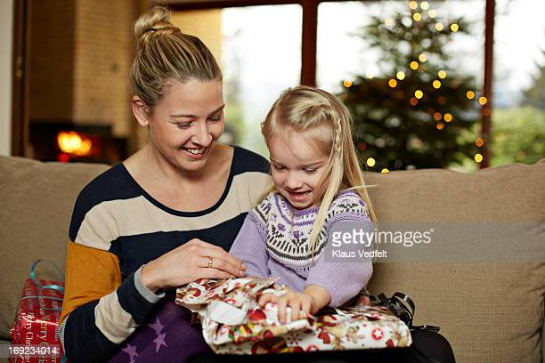 Mother helping daughter with opening present