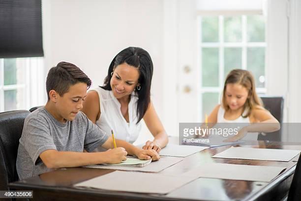 Madre ayudando a sus hijos con la tarea