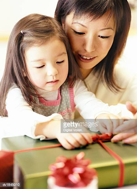 Mother helping Her Daughter Opening a Christmas Present