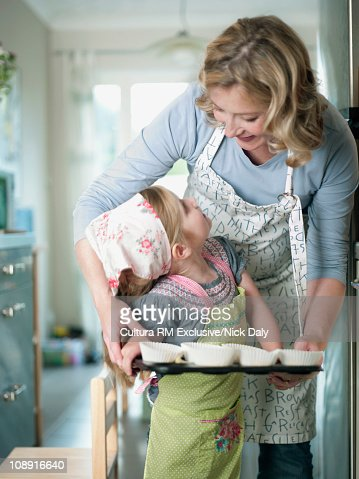 A mother helping her daughter to bake : Stock Photo