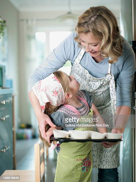 A mother helping her daughter to bake
