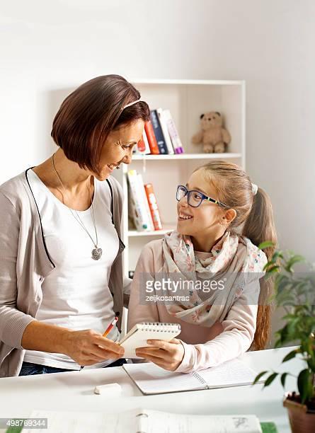 Mãe ajudando a filha com estudos