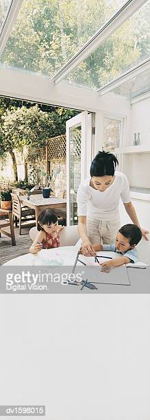 Mother Helping Her Son and Daughter to Colour In at the Kitchen Table