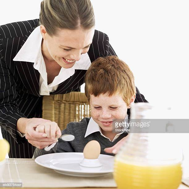 mother helping her son (6-7) eat an egg