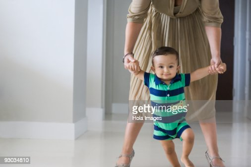 Mother helping her son in walking