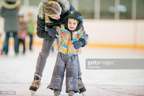 Madre aiutando suo figlio imparare a pattinare sul ghiaccio