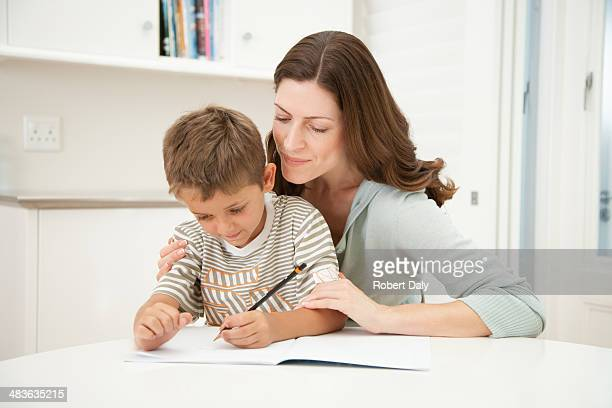 A mother helping her son with his homework