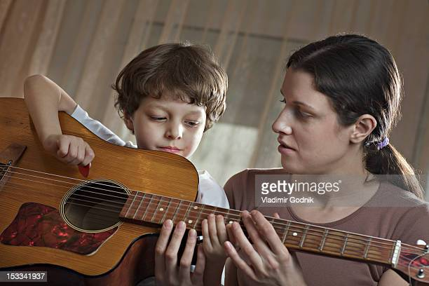 A mother helping her young son with playing an acoustic guitar