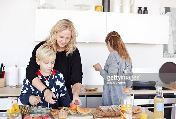 Mother helping kids with making breakfast