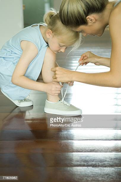 Mother helping little girl tie shoe laces