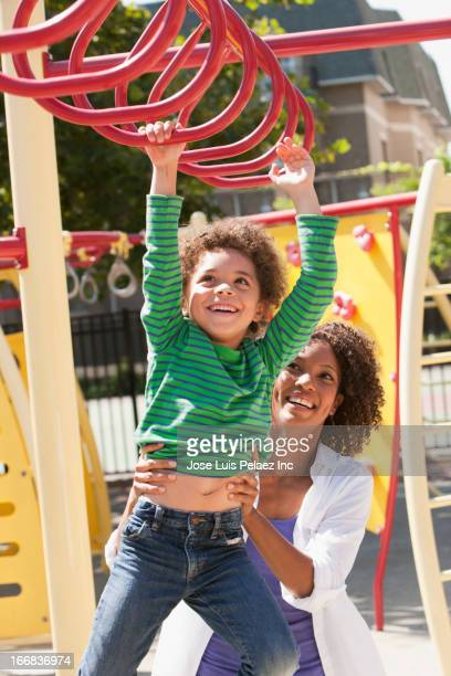 Mother helping son on jungle gym at playground