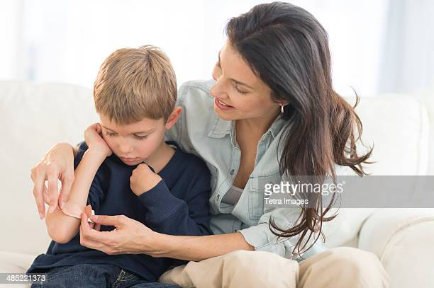 Mother helping son (6-7) put on bandaid