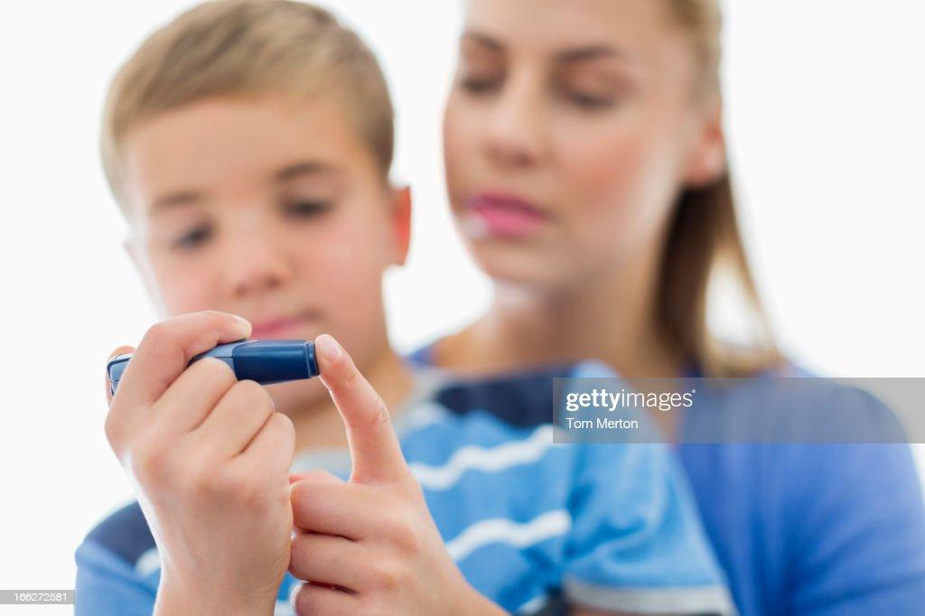 Mother helping son test blood sugar