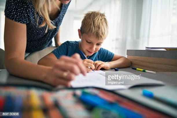 Mother helping son to do his homework