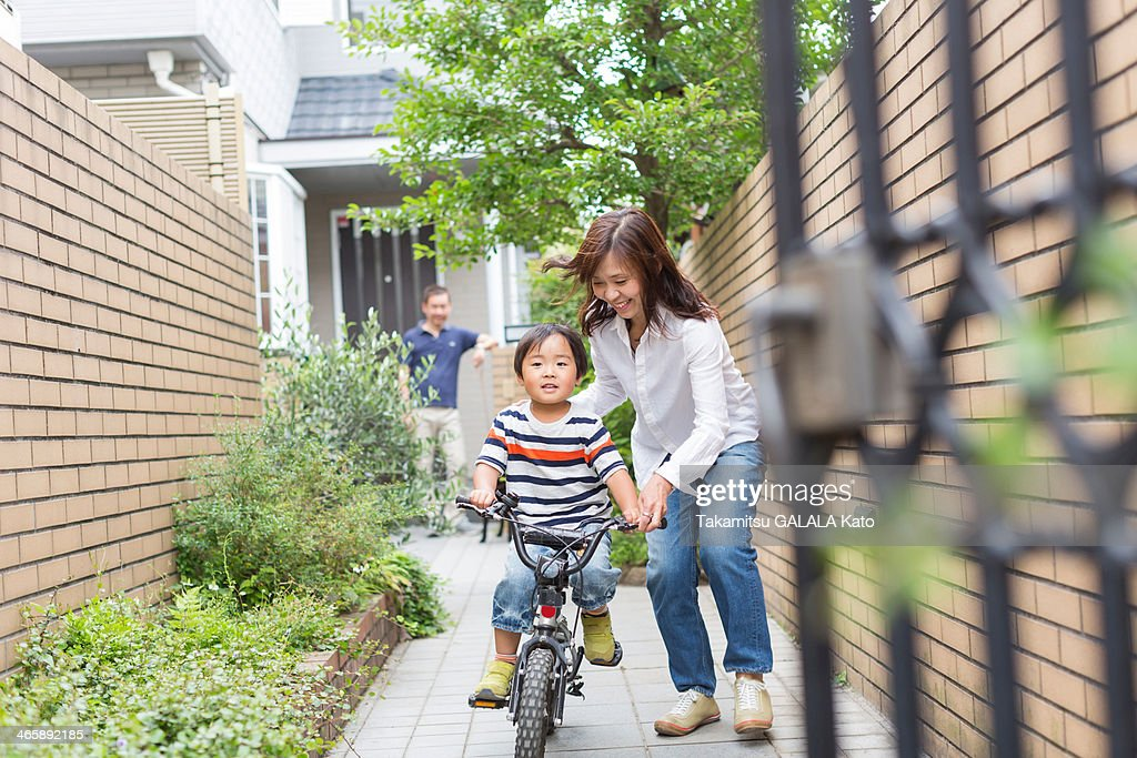Mother helping son to ride a bike