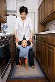Mother helping son walk in kitchen