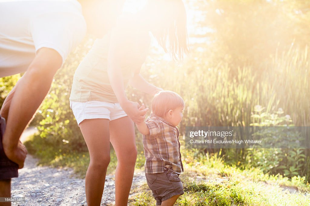 Mother helping son walk outdoors