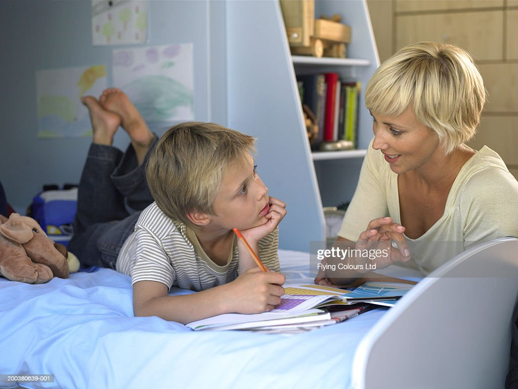 mother helping son with homework in bedroom stock photo