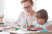 Back to school concept, young mother sitting at desk helping her little son with homework, boy is writing down in notebook