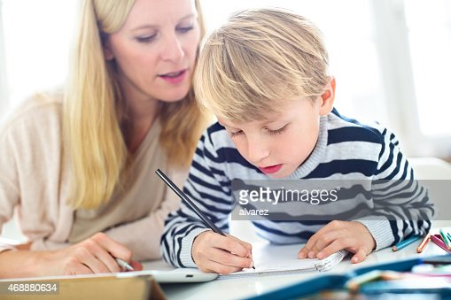 Mother helping son writing homework