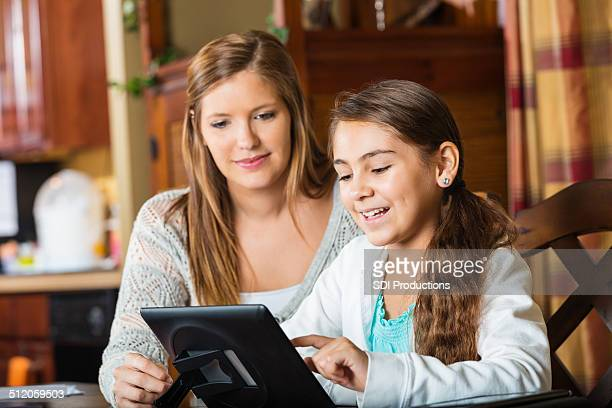 Mère aider jeune fille avec homeschool production