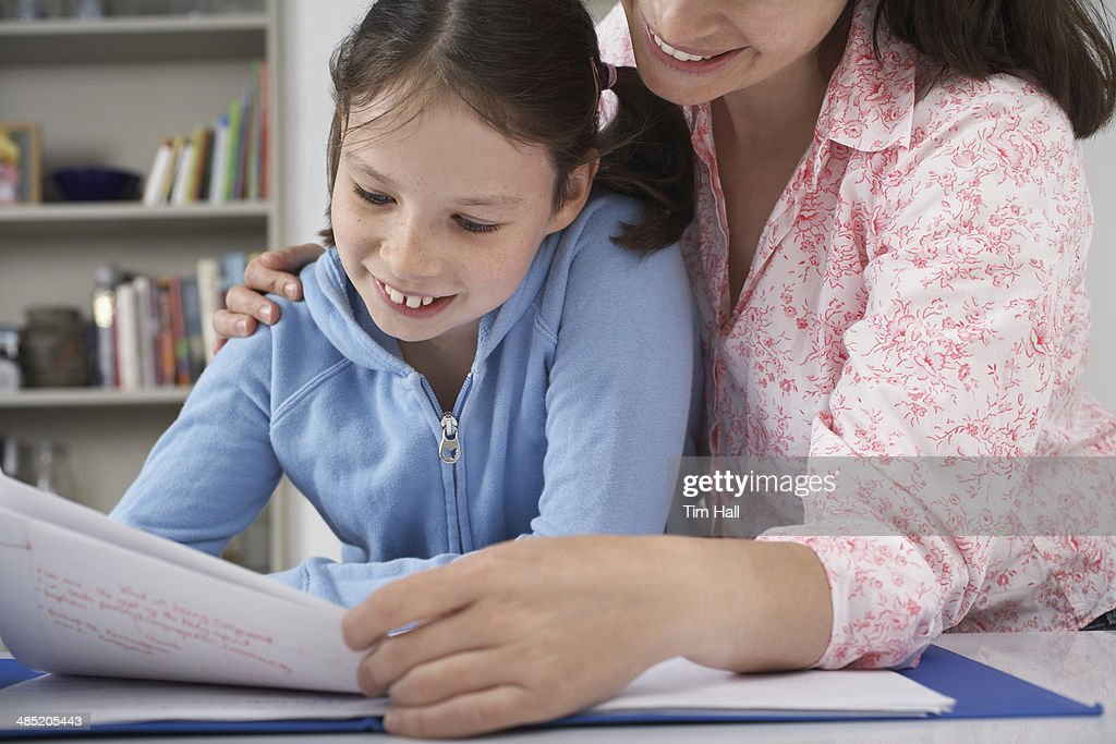 Mother helping young daughter with homework : Stock Photo