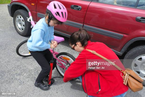 Mother helps her daughter to fill up air into her bicycle wheels