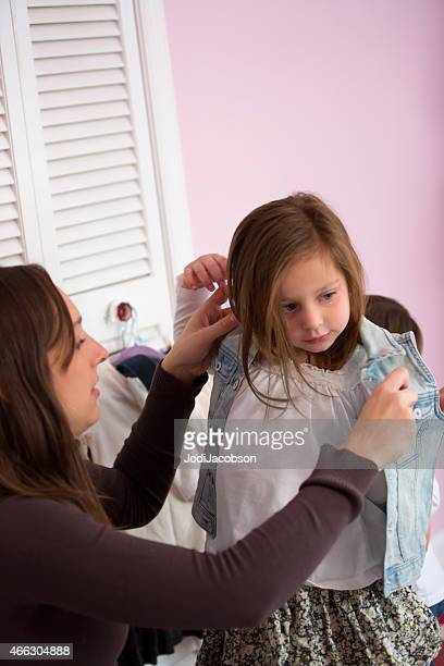 Mother helps her five year old daughter get dressed