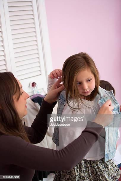 Madre aiuta la figlia di cinque anni per vestiti
